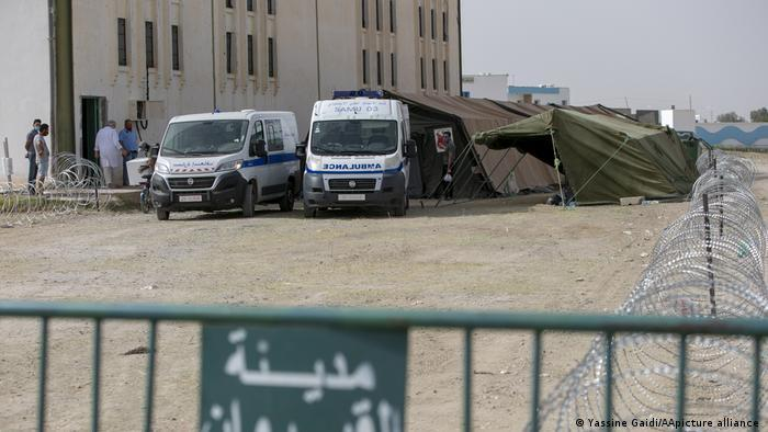 Two ambulances parked in front of two tents, building to the left, barbed wire to the right (photo: Yassine Gaidi/AA/picture-alliance)