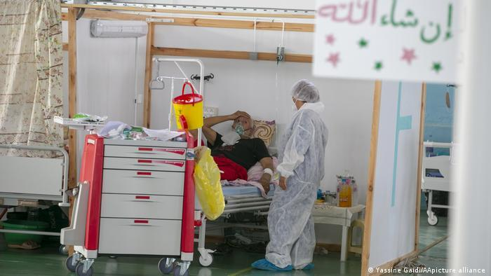 Person in a white protective suit looks at a patient in a bed in a makeshift cubicle, cart with medical appliances in the foreground (photo: photo: Yassine Gaidi/AA/picture-alliance)