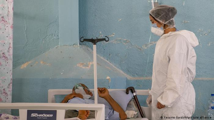 Person in a white protective suit, surgical cap and face mask looks at a patient in a bed in front of a rough pale blue wall (photo: Yassine Gaidi/AA/picture-alliance)