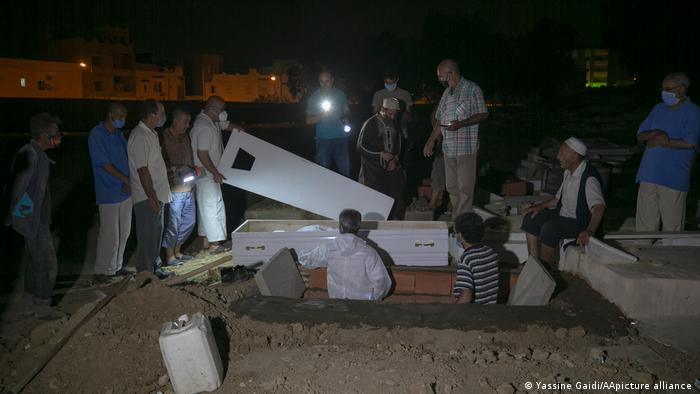 Men in a graveyard in the dark, one holding the lid of a coffin (photo: Yassine Gaidi/AA/picture-alliance)
