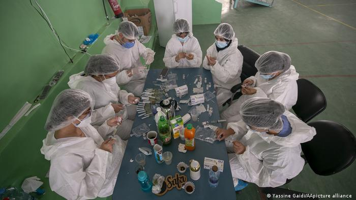 Seven people in protective suits, caps and masks sit around a table (photo: Yassine Gaidi/AA/picture-alliance)