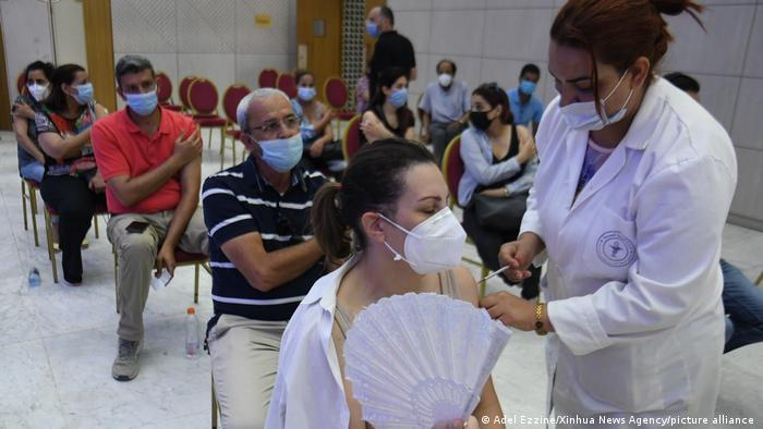 People sitting on chairs and wearing face masks, a woman in the foreground in being vaccinated by another woman (photo: Adel Ezzine/Xinhua News Agency/picture-alliance)