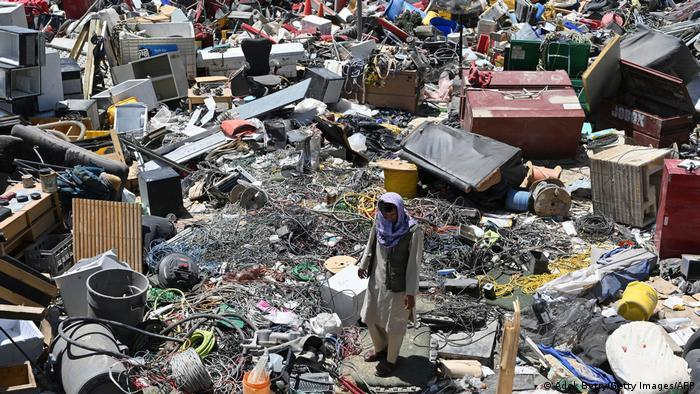 A man surrounded by scrap metal in Bagram