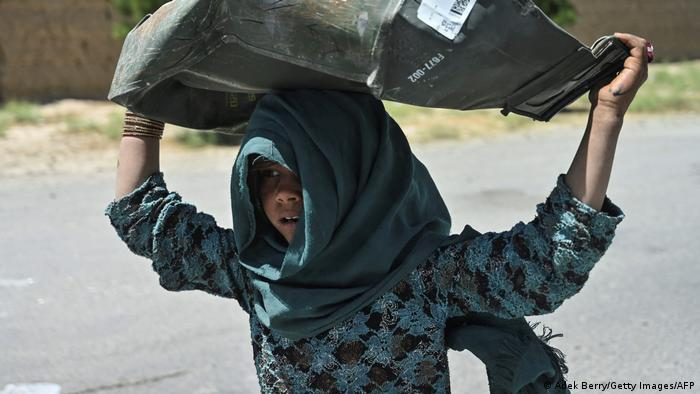 A girl picks up a dented metal box from the scrap yard in Bagram