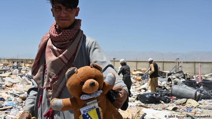 A man with a teddy bear on Bagram junkyard
