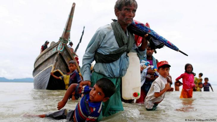 A Rohingya refugee man pulls a child as they walk to the shore after crossing the Bangladesh-Myanmar border by boat through the Bay of Bengal in Shah Porir Dwip, Bangladesh, 10 September 2017 (photo: REUTERS/Danish Siddiqui)
