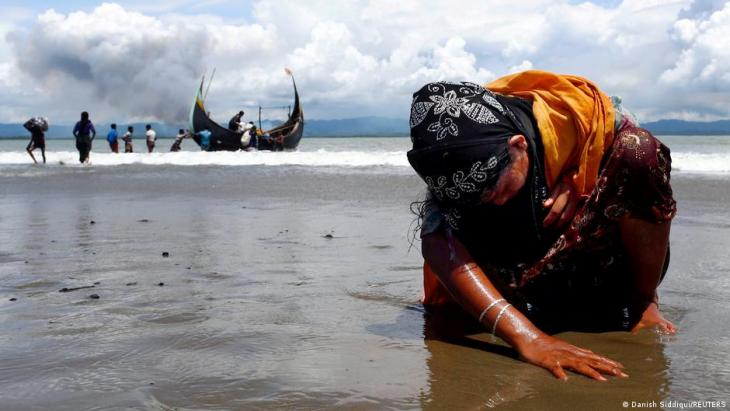 An exhausted Rohingya refugee woman touches the shore after crossing the Bangladesh-Myanmar border by boat through the Bay of Bengal, in Shah Porir Dwip, Bangladesh, 11 September 2017 (photo: REUTERS/Danish Siddiqui)