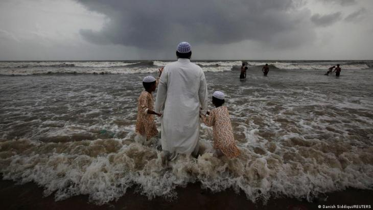A Muslim man walks hand in hand with children at a beach as monsoon clouds gather in Mumbai, 22 July 2011 (photo: REUTERS/Danish Siddiqui)