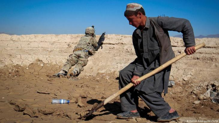 An Afghan boy works at a construction site as a U.S. Army soldier of 3/1 AD Task Force Bulldog takes position during a joint patrol with Afghan National Army (ANA) in a village in Kherwar district in Logar province, eastern Afghanistan, 23 May 2012 (photo: REUTERS/Danish Siddiqui)