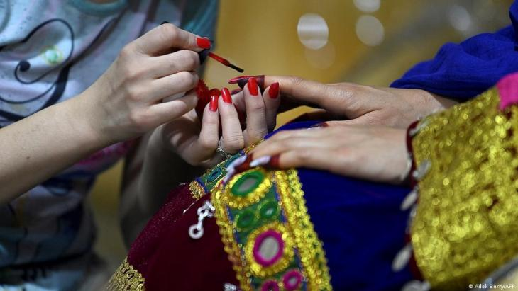 In this photo taken on 10 June 2021, a beautician paints the nails of a Pashtun bride for her marriage at a beauty parlour in Kabul (photo: Adek Berry/AFP)
