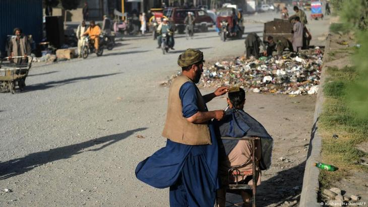 this photo taken on June 9, 2021, a barber cuts the hair of a customer along a road in Herat (photo: Hoshang Hashimi/AFP)