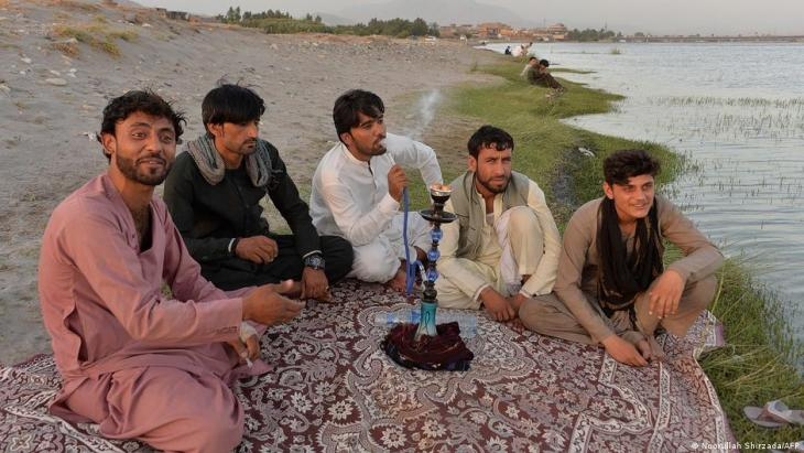 In this photo taken on 9 June 2021, men smoke a 'hookah' water pipe along a river on the outskirts of Jalalabad (photo: Noorullah Shirzada/AFP)