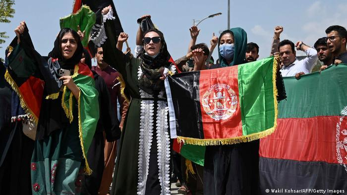 Afghans in Kabul holding up thier national flag in the street