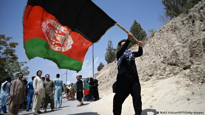 Afghan waving a large black, red and green national flag