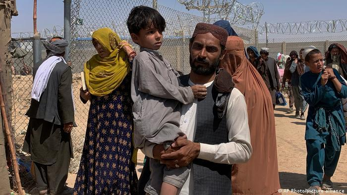 A man carrying a boy at the border crossing of Chaman