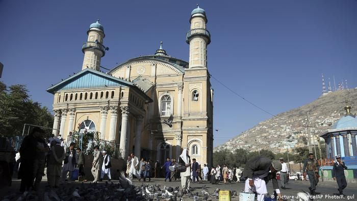 A classical-looking mosque against a backdrop of mountains; people walking past