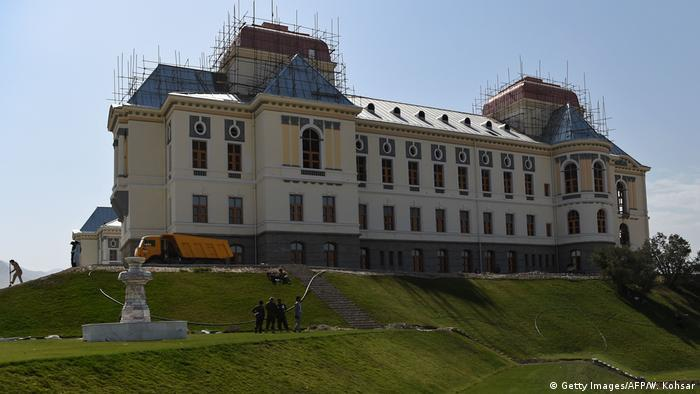 A grand building sits on a small hill with scaffolding its roof