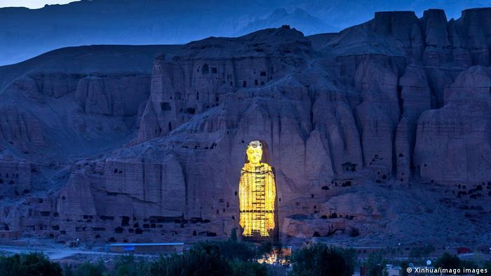 Projection of a shining golden Buddha figure in front of a mountain