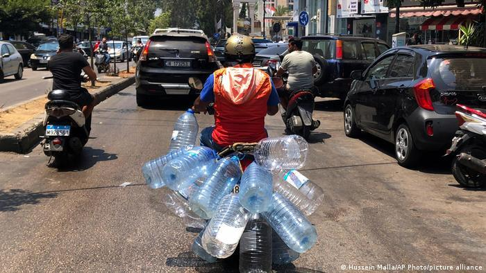 A man on a moped transports empty plastic water bottles.