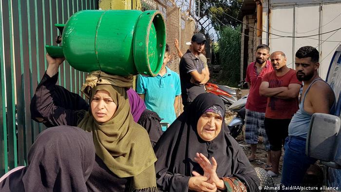 A Lebanese woman carries a gas canister on her head.