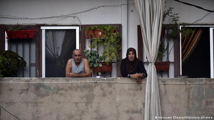 An elderly couple watch from their balcony in Beirut.