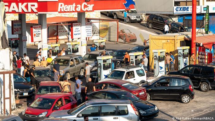 People and many cars wait at a petrol station in Lebanon.