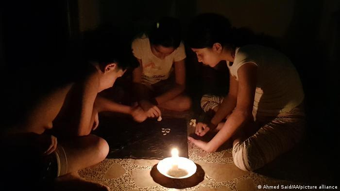 Children play a game by candlelight in Lebanon.
