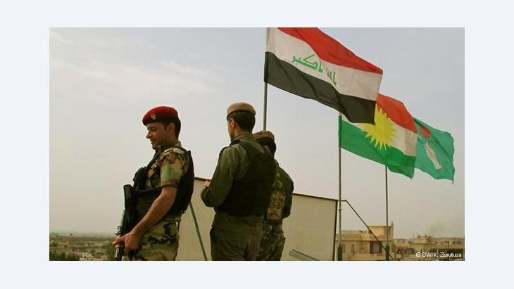 Soldiers seen standing in front of the Iraqi (left) and Kurdish (centre) flags (photo: DW/K. Zurutuza)
