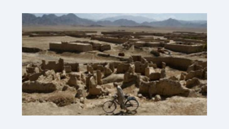 An Afghan youth rides his bycicle past houses that were destroyed during the Soviet occupation of Afghanistan (photo: picture alliance/dpa)