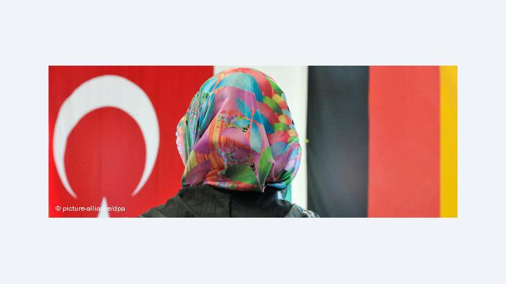 Woman with headscarf, a Turkish and a German national flag in the background (photo: picture-alliance/dpa)