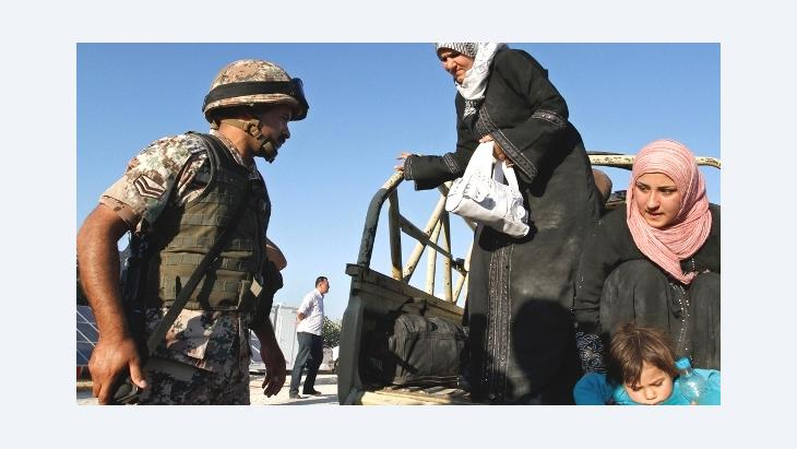 In this Saturday, Sept. 15, 2012 photo, a Jordanian soldier helps Syrian refugees who have fled violence in their country after having crossed the border into Jordanian territory with their families near the town of Ramtha, Jordan, September 15, 2012 (photo: Raad Adayleh/AP)