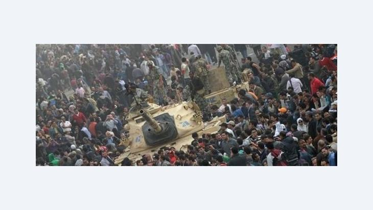 A crowd surrounding an Egyptian military tank at Tahrir Square in Cairo (photo: dpa)
