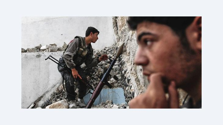 A rebel fighter keeps an eye out for Syrian regime forces as they plan to attack and neutralize a tank positioned on the street ahead in the Karmel al-Jabl district of Aleppo, on October 31, 2012 (photo: Javier Manzano/AFP/Getty Images9