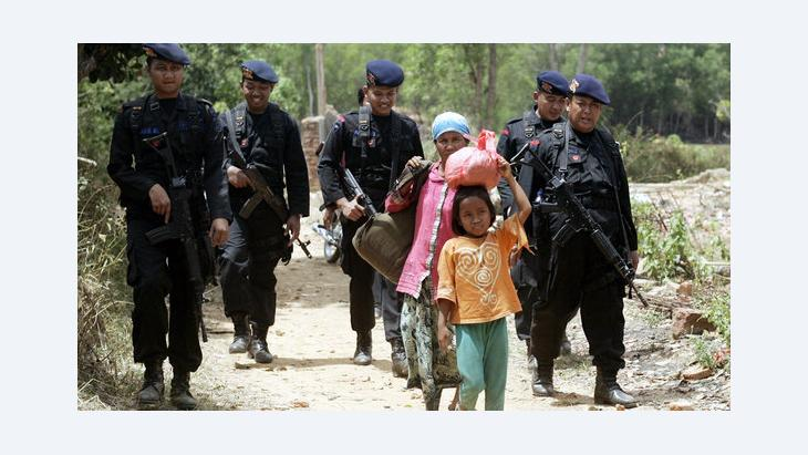 Indonesian Shia Muslims are escorted by police officers as they flee their village following sectarian violence in August 2012 (photo: picture-alliance/dpa)