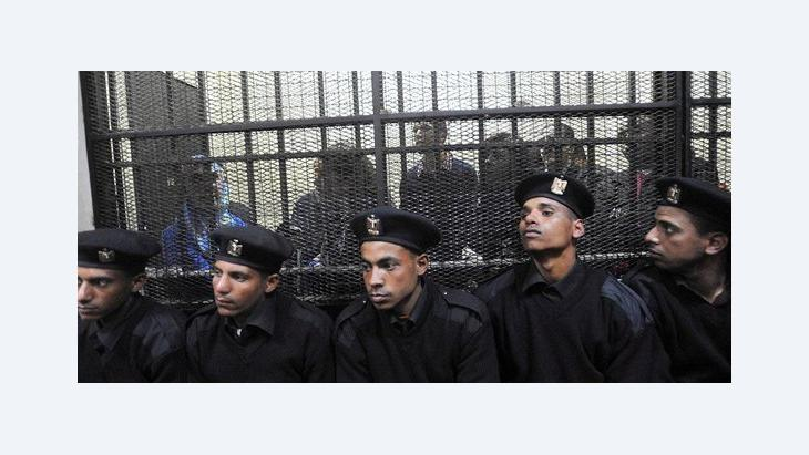 The Foundation's local staff in the Cairo courtroom, behind bars (photo: EPA)