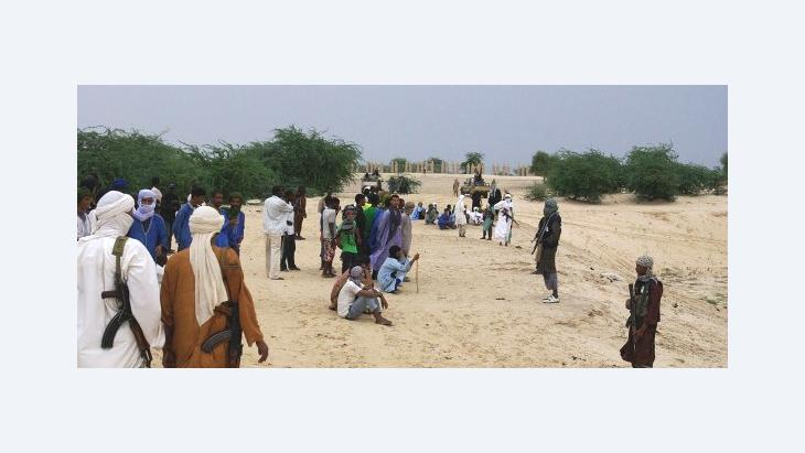 In this Sunday, Sept. 16, 2012 photo, armed fighters from Islamist group Ansar Dine stand guard between onlookers and the area where Ansar Dine was preparing to amputate the hand of a young man found guilty of stealing rice, in Timbuktu, Mali (photo: AP)