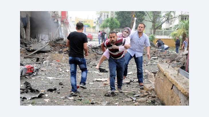 People help victims after an explosion in Reyhanli District, Hatay, Turkey, 11 May 2013. At least 13 people were killed and 22 wounded following explosions on 11 May in southern Turkey near the Syrian border (photo: picture-alliance/dpa)