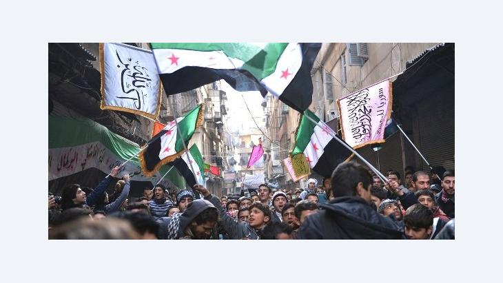 Syrian anti-regime protesters wave pre-Baath Syrian flags, now used by the Free Syrian Army, during a demonstration after the weekly Friday prayers in the Bustan al-Qasr district of the northern city of Aleppo on February 8, 2013 (photo: Aamir Qureishi/AFP/Getty Images)