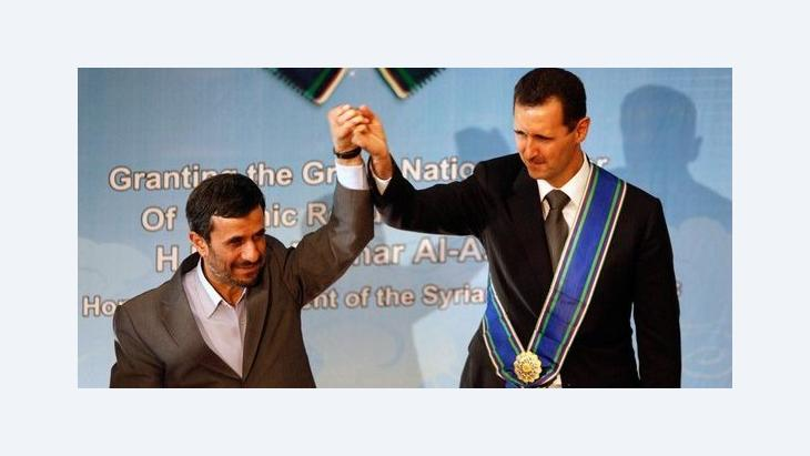 In this Oct. 2, 2010 file photo, Iranian President Mahmoud Ahmadinejad, left, holds up the hand of his Syrian counterpart Bashar Assad after he awarded Iran's highest national medal to Assad, in a ceremony in Tehran, Iran (photo: AP)