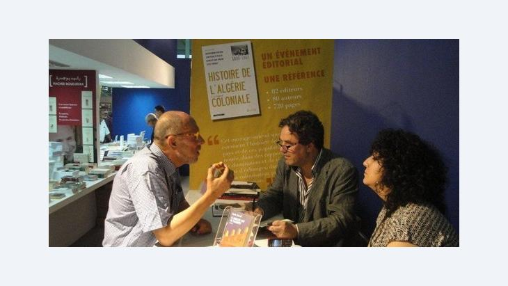 The Algerian writer Amin Zaoui (right) discussing with an attendee of the Algiers Book Fair (photo: Marina Sabra)