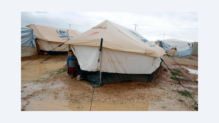 A Syrian refugee boy looks out of his parents' tent after heavy rain at the Al-Zaatari refugee camp, Jordan near the border with Syria (photo: REUTERS/Ali Jarekji)