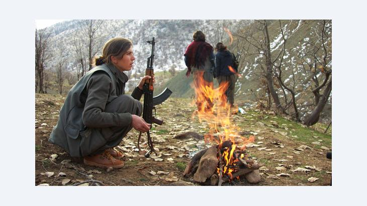 A member of the PKK warms herself by the fire at a camp in the Qandil mountains near the Turkish border with northern Iraq (photo: AP)