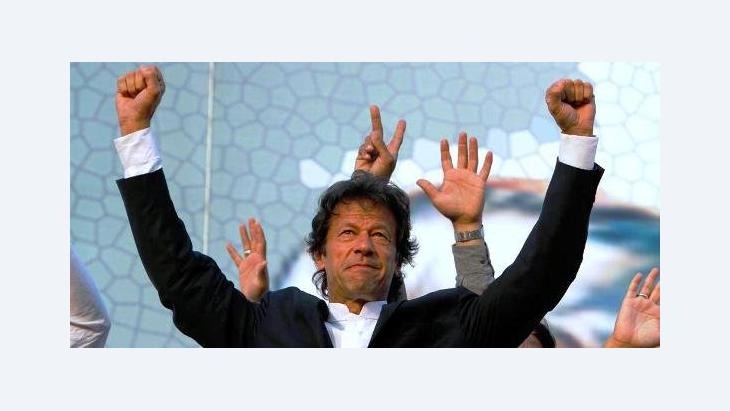 Pakistani cricketer turned politician and head of Pakistan Tahreek-e-Insaf or Movement for Justice Party Imran Khan waves to his supporters during a rally in Lahore, Pakistan, 30 October 2011 (photo: AP)