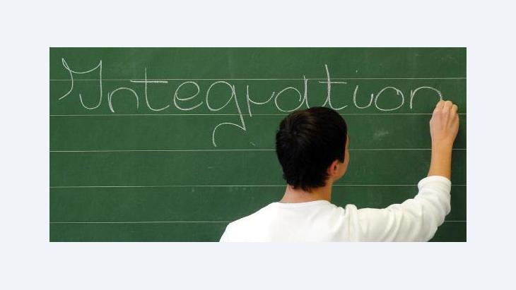 "Schoolboy writes the word ""Integration"" on a chalk board (photo: dpa)"