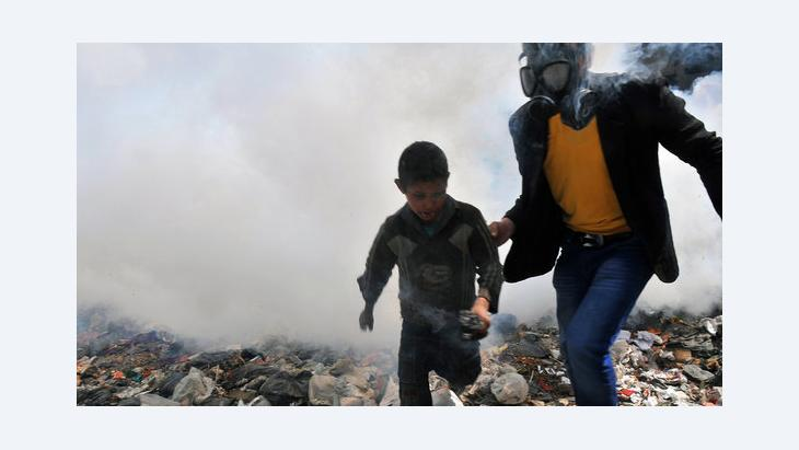 A man wearing a gas mask and a boy run away from a combat zone in Aleppo, Syria (photo: Getty Images/AFP)