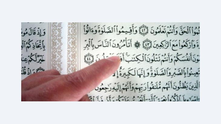 A finger pointing at verses of the Koran (photo: Ulrike Hummel/DW)