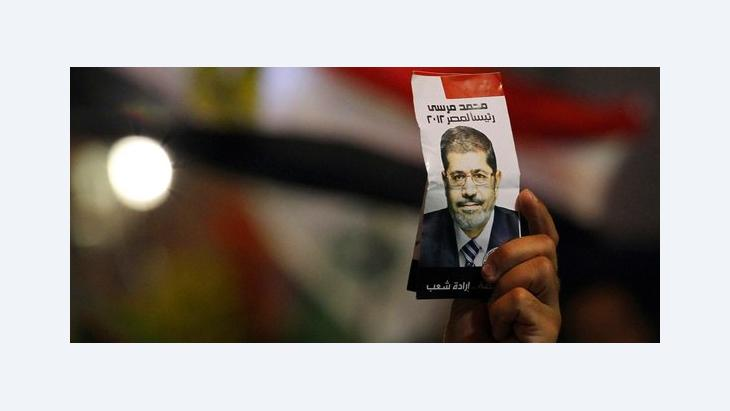 A man holds up an election leaflet, picturing Mohammed Morsi (photo: Reuters)