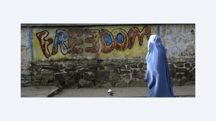 A woman wearing Burqa walking in front of 'freedom' graffiti (photo: AP)