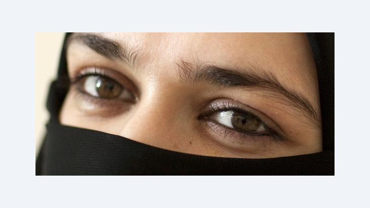 A veiled woman looking at the camera (photo: dpa)