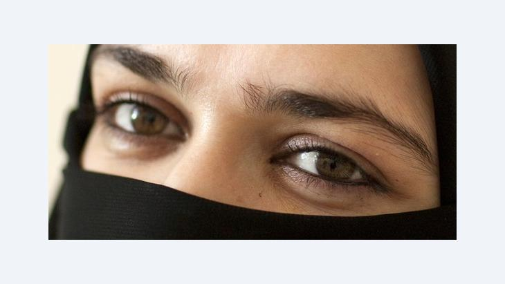 A veiled woman looking at the camera (photo: dpa)